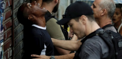 30jan2018---homem-revistado-durante-operacao-policial-no-jacarezinho-favela-da-zona-norte-carioca-abre-boca-e-levanta-a-cabeca-para-que-agentes-da-policia-civil-verifiquem-se-ele-possui-